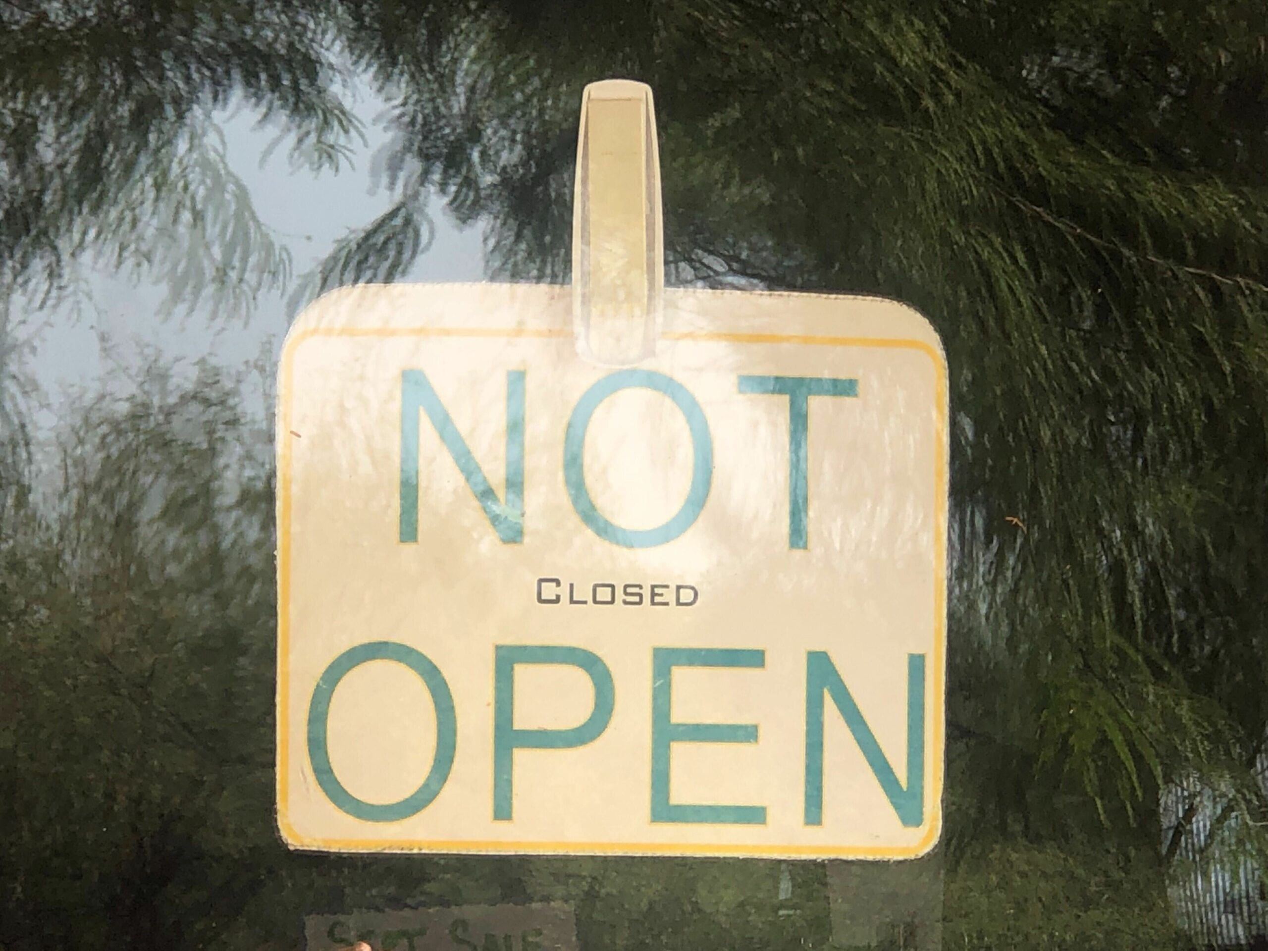 "A sign in a window reads, ""NOT OPEN"" in large letters, in small letters in between it reads, CLOSED"